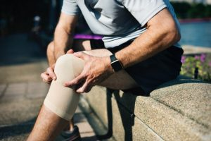 Sports Injury - sports supporters injury - Personal Injury Claims Solicitor Doherty Solicitors. Man holding knee injured.